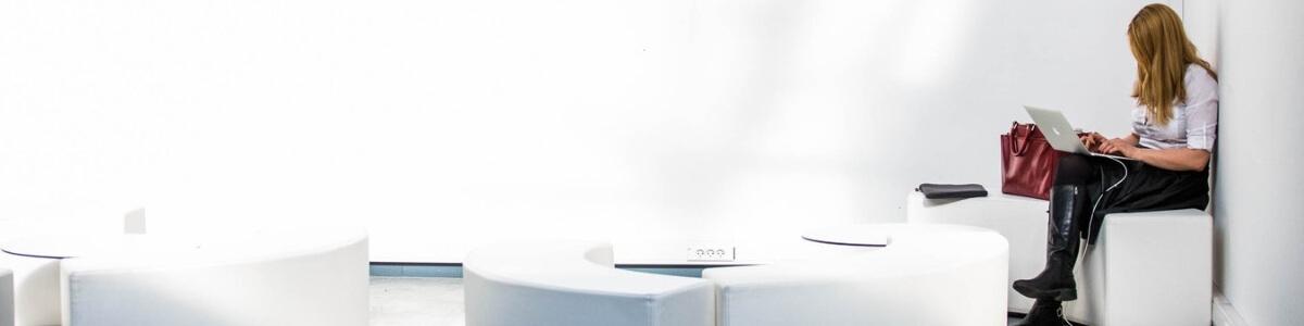 Frau auf weißem Lounge-Hocker am Arbeiten mit dem Notebook