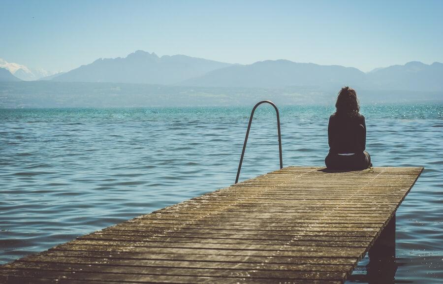 Frau sitzt auf Steg am See in der Schweiz